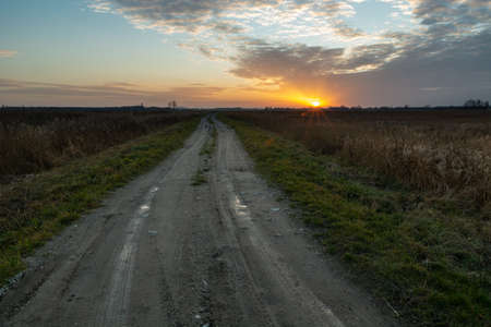 Straight and long dirt road and sunset