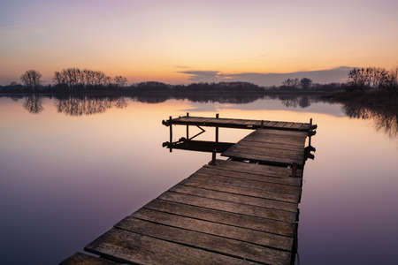 Wooden jetty and calm water surface on the lake, trees on the horizon, view after sunset
