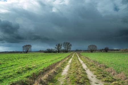 Spring storm dark clouds and a dirt road through green fields Stock fotó