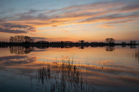 Reflection of clouds in the water after sunset, March evening at the lake Banque d'images