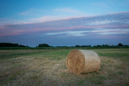 Hay bale in a meadow and colorful clouds on the sky, summer evening view