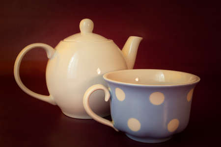 Porcelain kettle with tea cup, maroon background Stockfoto