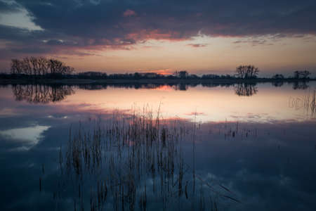 Reflection of clouds after sunset in a quiet lake, spring view Stok Fotoğraf