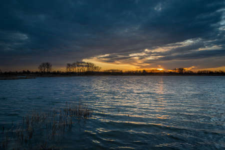Sunset and dark clouds over the lake with reeds, spring evening view