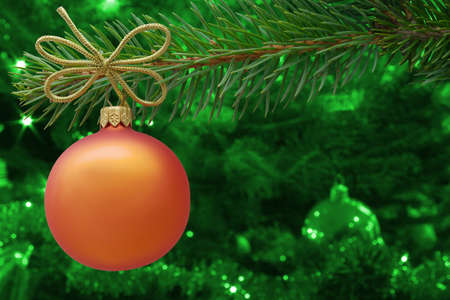 Christmas bauble and spruce branch on green background photo