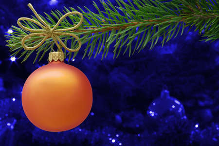 Christmas bauble and spruce branch on blue background photo