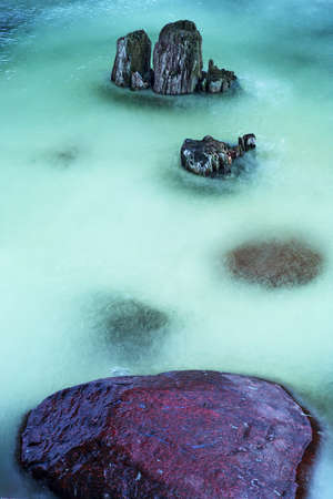 pales: Stones and old wooden pales in frozen river