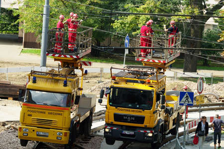 Warsaw, Poland - August 31, 2014 : Workers in crane baskets repairing the tram power grid on 11 Listopada street in Warsaw.