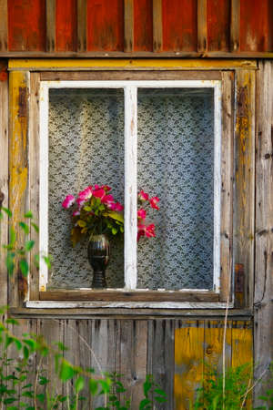 Red roses in a vase standing on a window sill of an old wooden cottage. photo