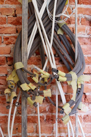 plastic conduit: Close up of tangled electrical conduits on the brick wall. Stock Photo