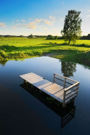 Rural summer landscape with wooden platform in the river and green meadows. Podlasie region, north-eastern Poland.