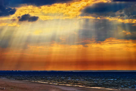 dawns: Cloudscape with crepuscular rays or sunbeams over the Baltic sea. Stegna, Pomerania, northern Poland.
