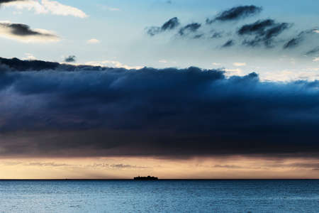 dawns: Cloudscape with huge nimbostratus dramatic cloud formation over Baltic sea and small silhouette of ship on the horizon. Pomerania, Poland.