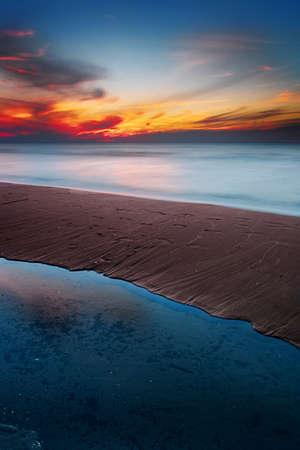 Beautiful sunset at Baltic sea beach. Waves blurred by long exposure. Gdansk Bay, Pomerania, Poland. Stock Photo