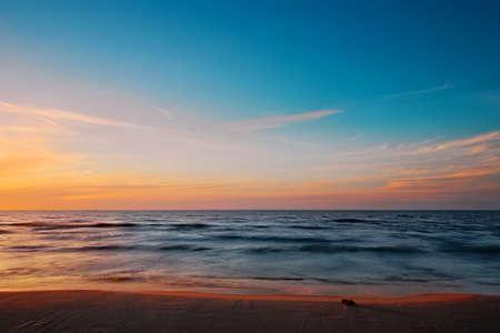 Beautiful twilight at Baltic sea beach. Waves blurred by long exposure. Gdansk Bay, Pomerania, Poland.