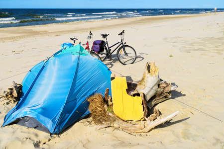 campsite: Blue tent and bicycles on a deserted sandy beach. Camp at the Baltic sea coast. Bicycle tourism. Stegna, Pomerania, Poland.