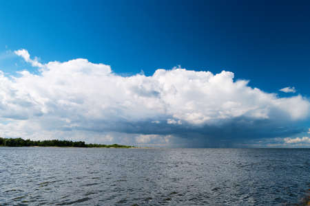 Estuary of the Vistula River to the Baltic Sea with the Cumulus mediocris cloud in the sky. Pomerania, Poland.