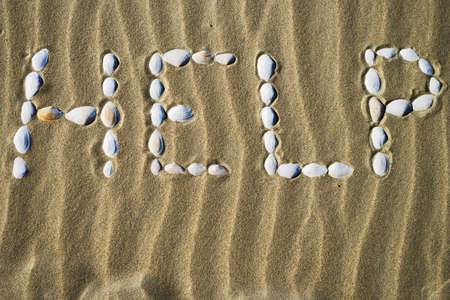 The word Help made of white seashells on sand. Calling for help in danger.