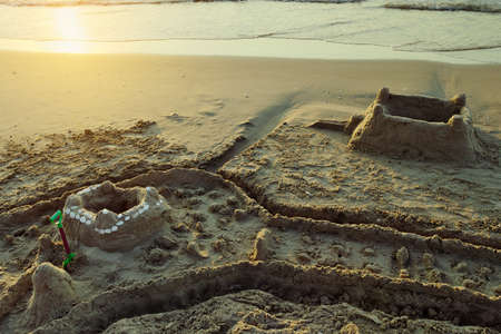 Sandcastle with moat on the Baltic beach at dusk. Summer vacation, leisure activity. Pomerania, Poland.