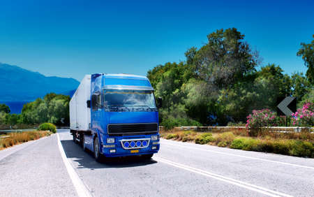 Cargo truck on the mountain highway with blue sky and sea on a background photo