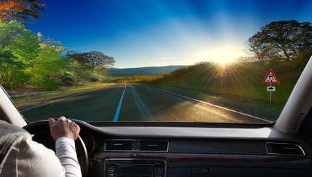personas en la calle: Las manos en el volante de un coche de conducci�n en una carretera de asfalto Foto de archivo