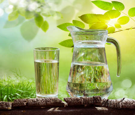 Glass of water on nature background.