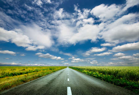 image of wide open prairie with a paved highway stretching out as far as the eye can see with beautiful small green hills under a bright blue sky in the summer time