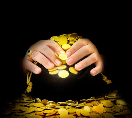 greedy: greedy hands guarding the bag of gold coins Stock Photo