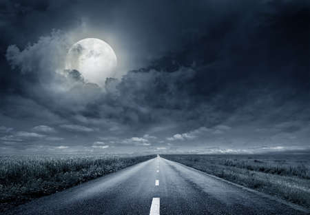 end of road: asphalt road night bright illuminated large moon Stock Photo