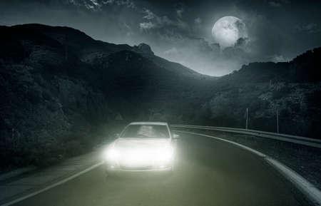 Conduciendo por una carretera asfaltada hacia los faros de un coche en la noche Foto de archivo - 49992225