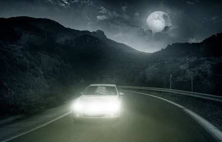 locomotion: Driving on an asphalt road towards the headlights of car at night