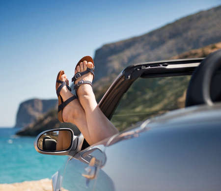 summer fun: female legs dangling from the open car window in the shales Stock Photo: Image ID: 146438690