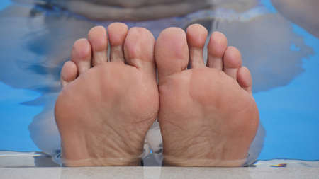 painted toes: Feet in the pool close-up outdoors.