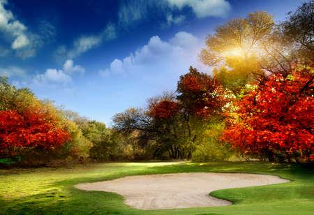 of course: Autumn Foliage at the Golf Course - The sun shines on a putting green and lake at a golf course in Autumn. Stock Photo