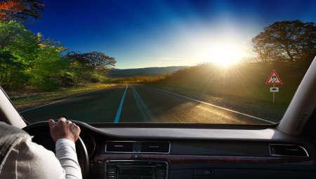 Mains sur le volant d'une voiture circulant sur une route goudronnée