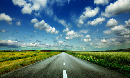 long distance: image of wide open prairie with a paved highway stretching out as far as the eye can see with beautiful small green hills under a bright blue sky in the summer time