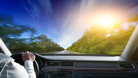 car front: Driver in car holding steering wheel. Blurred road and sky Stock Photo