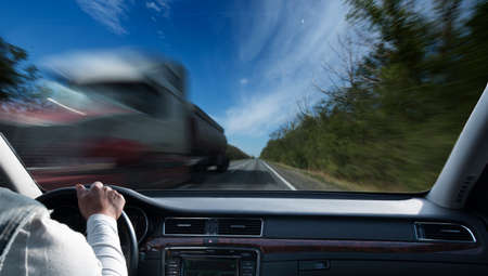 Driver in car holding steering wheel. Blurred road and sky Foto de archivo