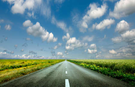 as far as the eye can see: image of wide open prairie with a paved highway stretching out as far as the eye can see with beautiful small green hills under a bright blue sky in the summer time