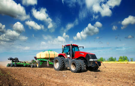 plough machine: tractor in a field plowing