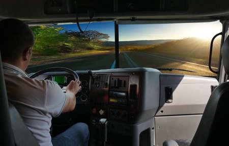 De vrachtwagenchauffeur op de weg tussen velden snelweg. zakenreis Stockfoto