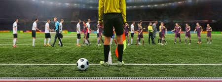 De scheidsrechter voetbalspel staat op het veld voor de wedstrijd, klaar om het fluitje blazen. Soccer Team begroeten elkaar in het stadion voor de wedstrijd