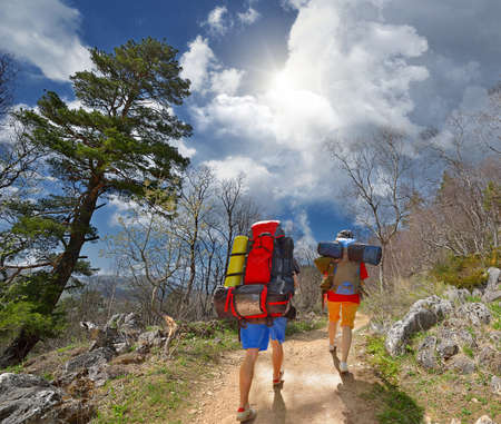 Two backpackers in mountains. Stock Photo
