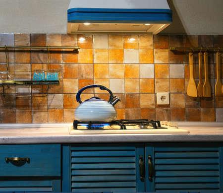 nueva caldera de ebullición silbido del metal en la cocina. La cocina moderna es de color azul.