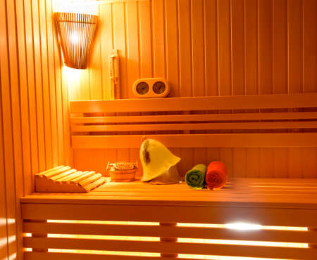 finnish bath: Sauna. Bathroom Accessories: bucket, spoon carving, hat, rolled in a roll towel and a vase of scented candles.