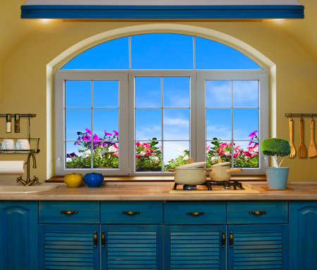 worktops: Interior blue kitchen. Preparing lunch at home on the kitchen stove with a view from the window of the green meadows and fields Stock Photo