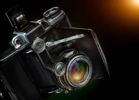 old photograph: Old camera on a black background. Vintage Stock Photo