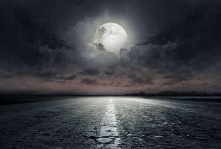 Landweg 's nachts met grote maan Stockfoto