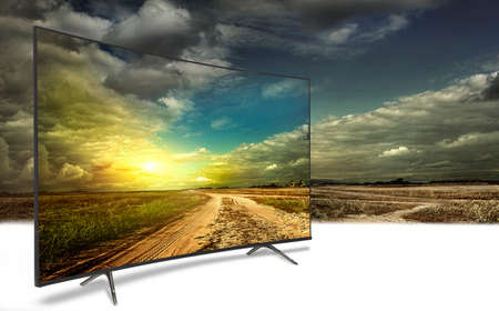 4k monitor isolated on white.  The road is rural, unpaved in the steppes at sunset. Concept