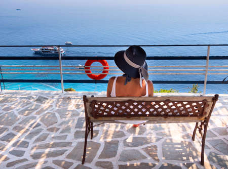 A woman is resting on a bench with a view of the Ionian Sea and ships with tourists, Zakynthos island